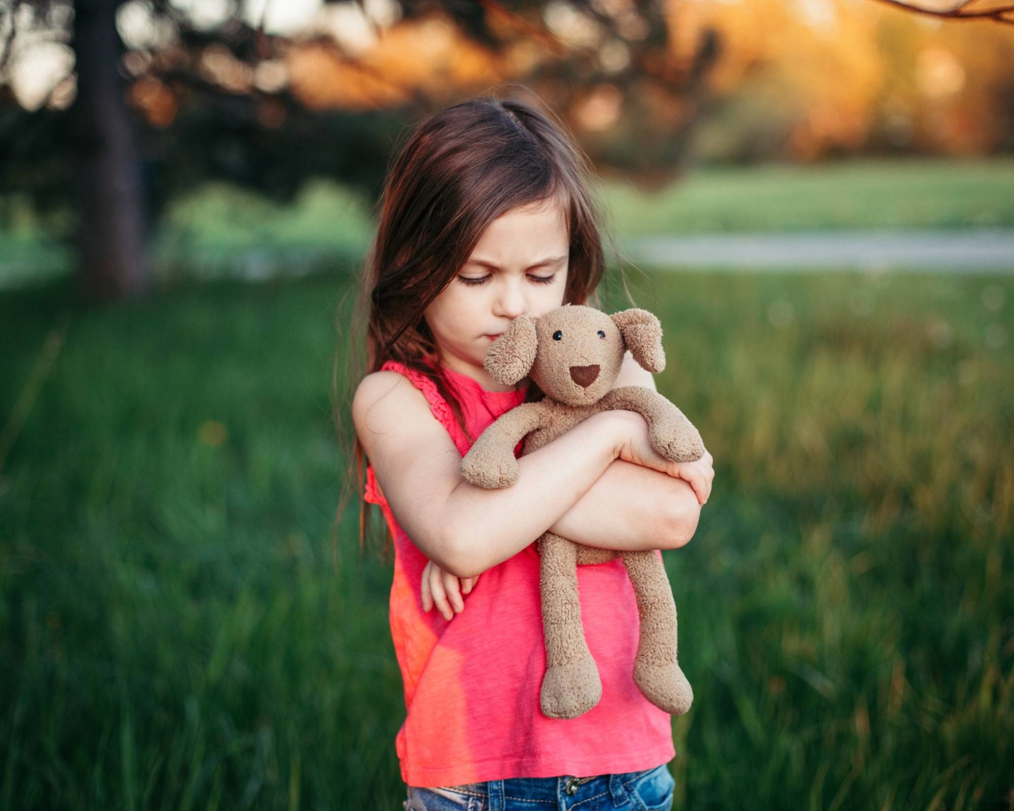 girl hugging stuffed animal dog